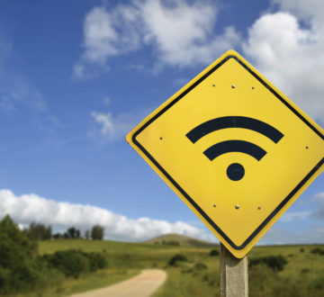 Internet access in remote zone, power of technology concept. Road sign with wifi signal icon on rural environment